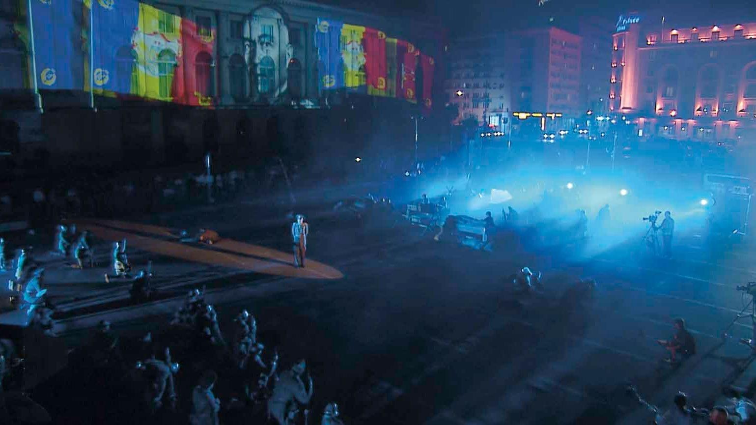 Man sieht einen großen Platz bei Nacht, auf dem ein Theaterstück aufgeführt wird.