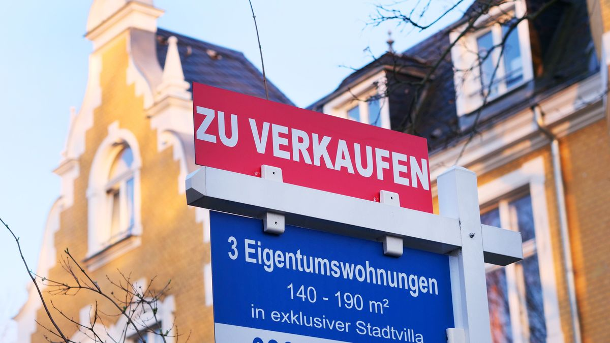 """Ein """"Zu verkaufen""""-Schild steht vor einem Wohnhaus."""