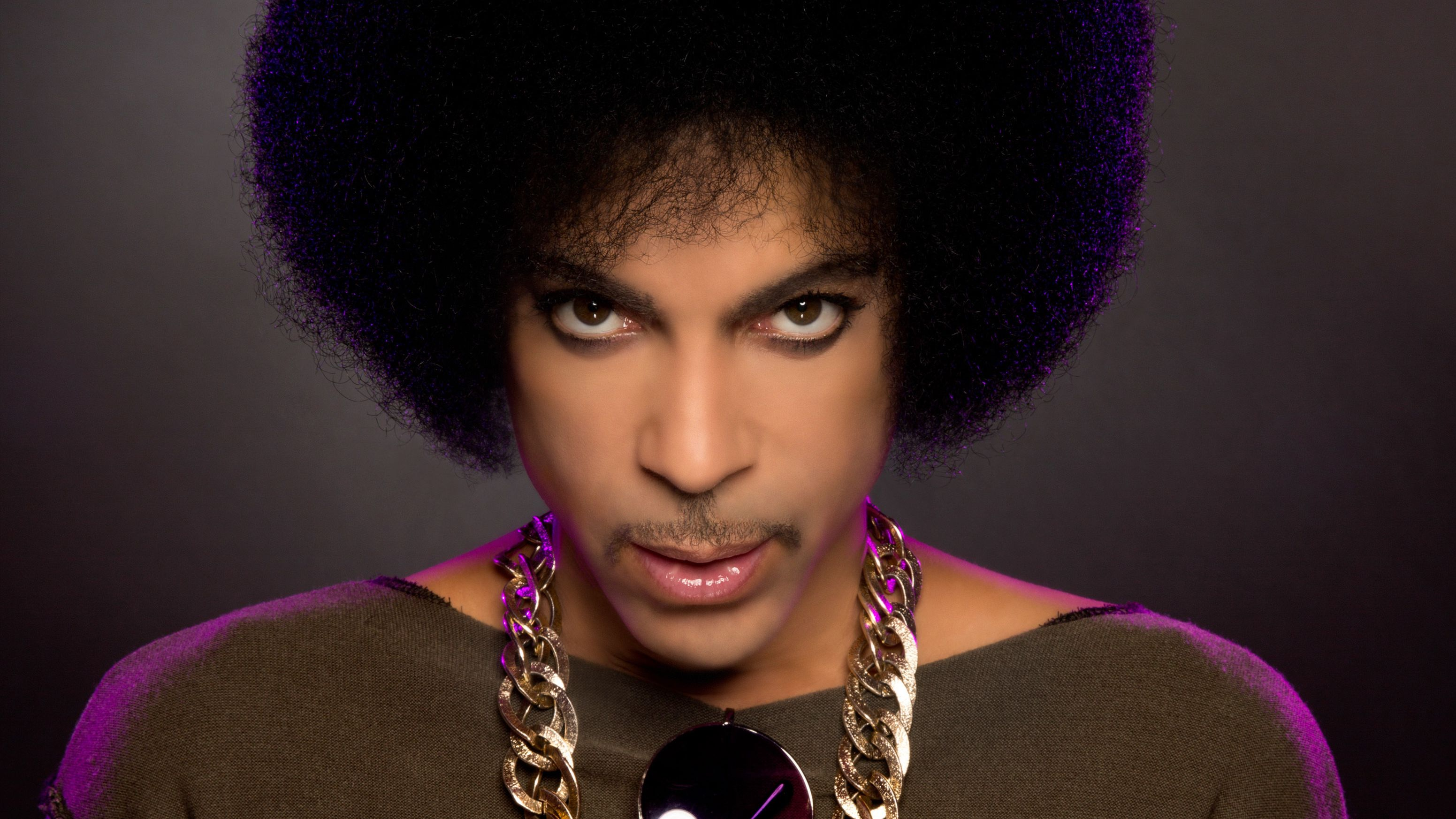 Popgenie Prince blickt, von hinten mit lilafarbenem Licht beleuchtet, intensiv in die Kamera (PR-Aufnahme 2014)