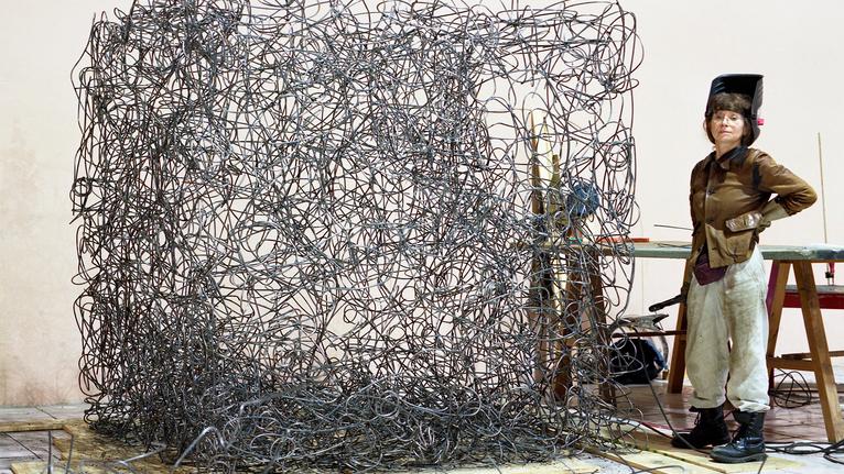 Künstlerin Angelika Summa steht neben einem Kunstwerk.