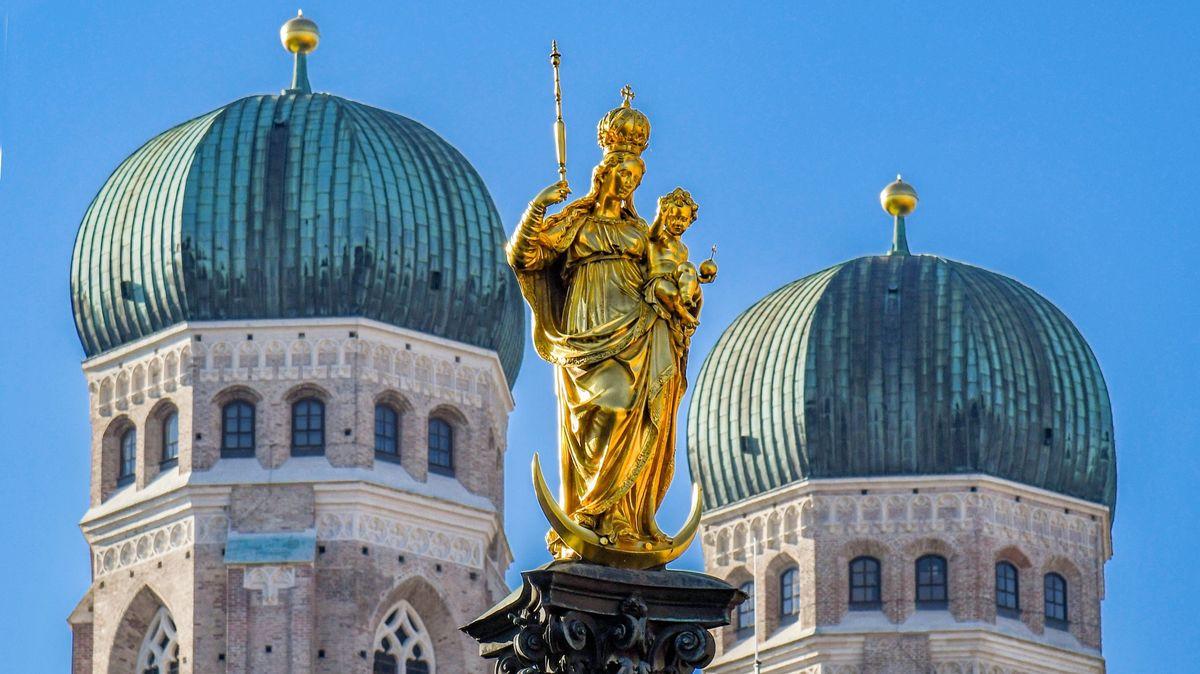 Die Turmspitzen der Münchner Frauenkirche, davor die Marienstatue vom Marienplatz.