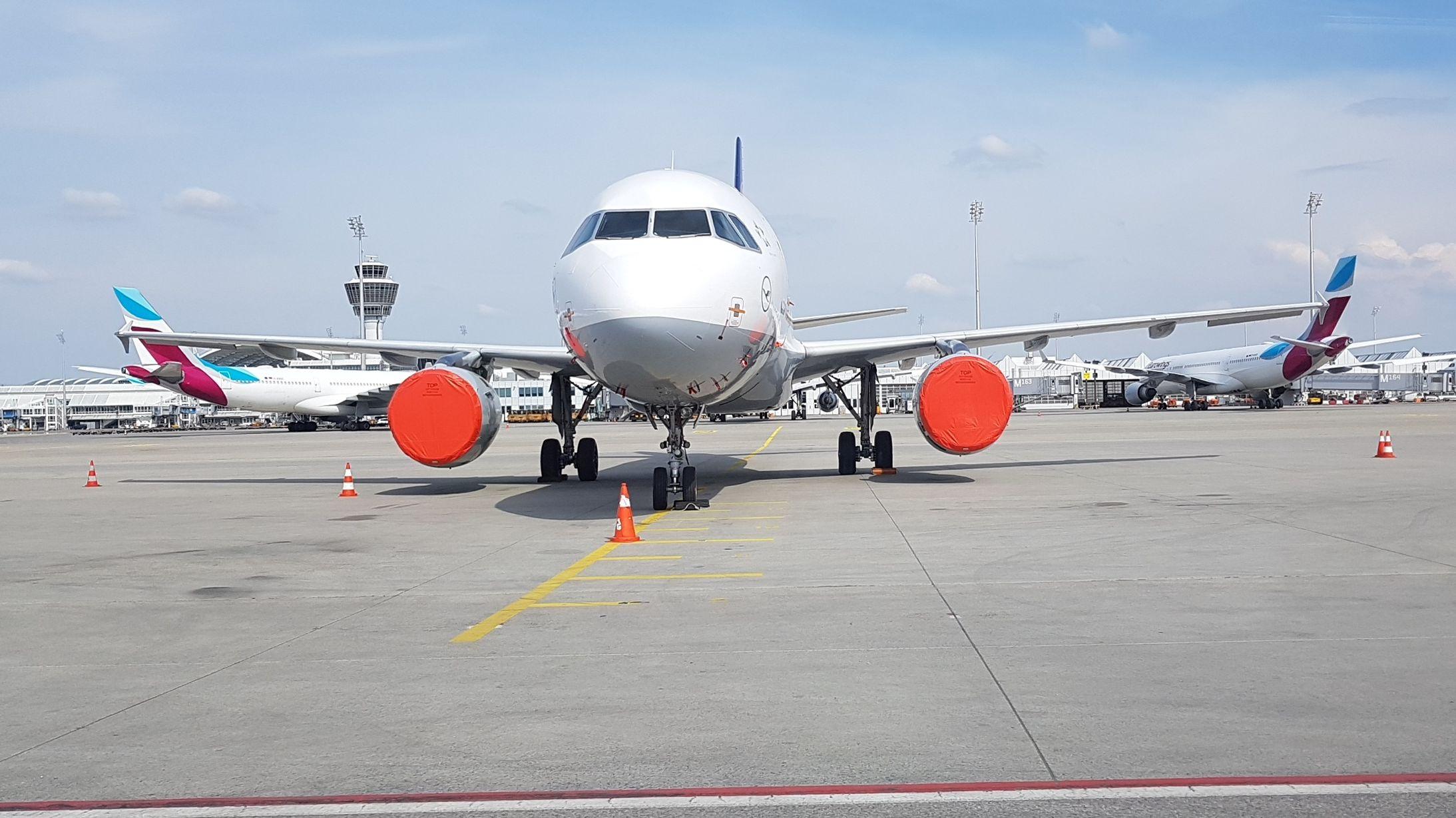Geparktes Flugzeug am Flughafen mit roter Abdeckplane