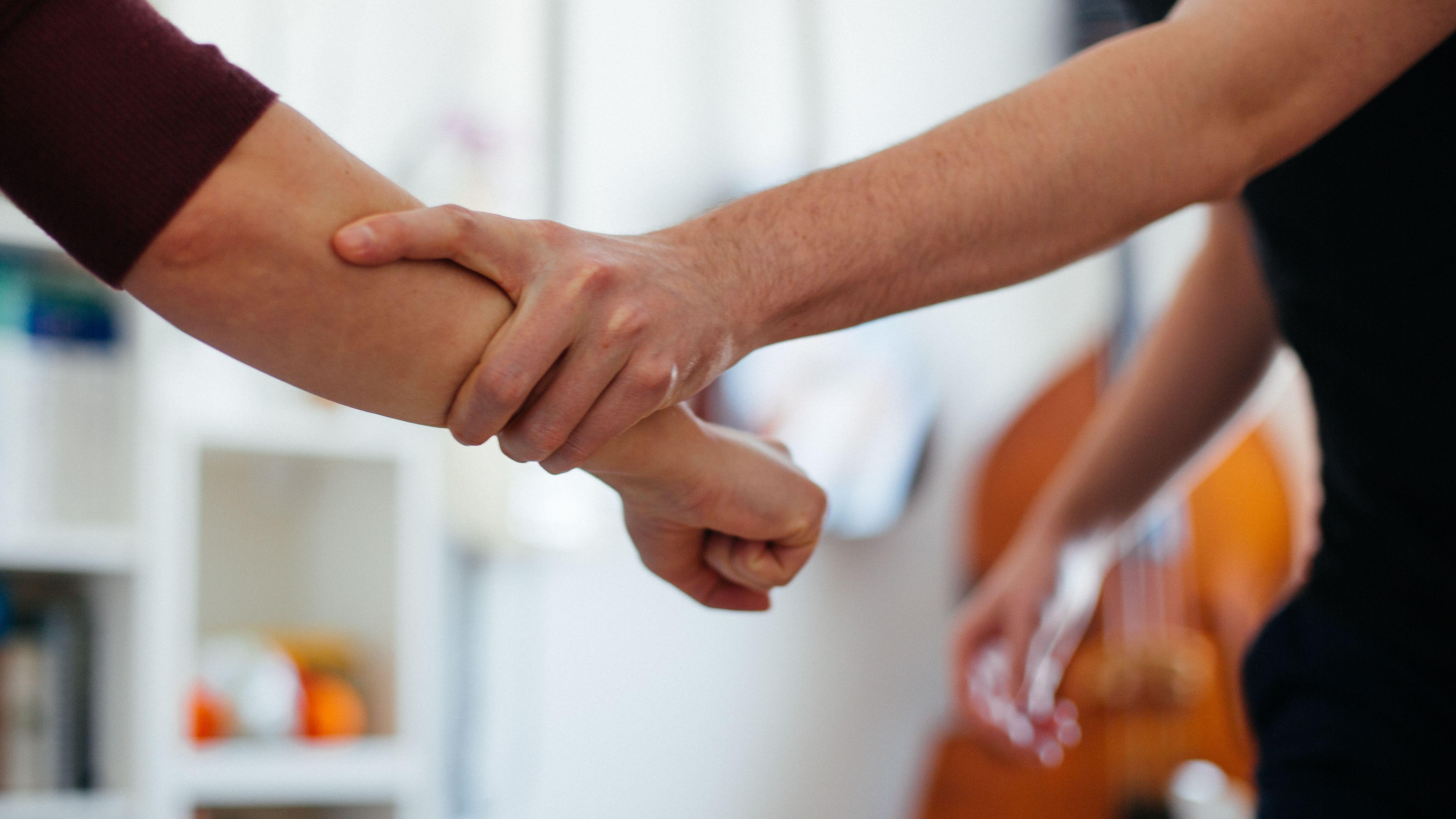 Symbolbild Gewalt; Ein Mann versucht einen Arm mit geballter Faust zurückzuhalten