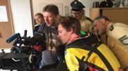 Regisseur, Schauspieler und Polizeibeamte schauen in einer Polizeistation durch das Objektiv einer Filmkamera   Bild:BR/Kristina Kreutzer
