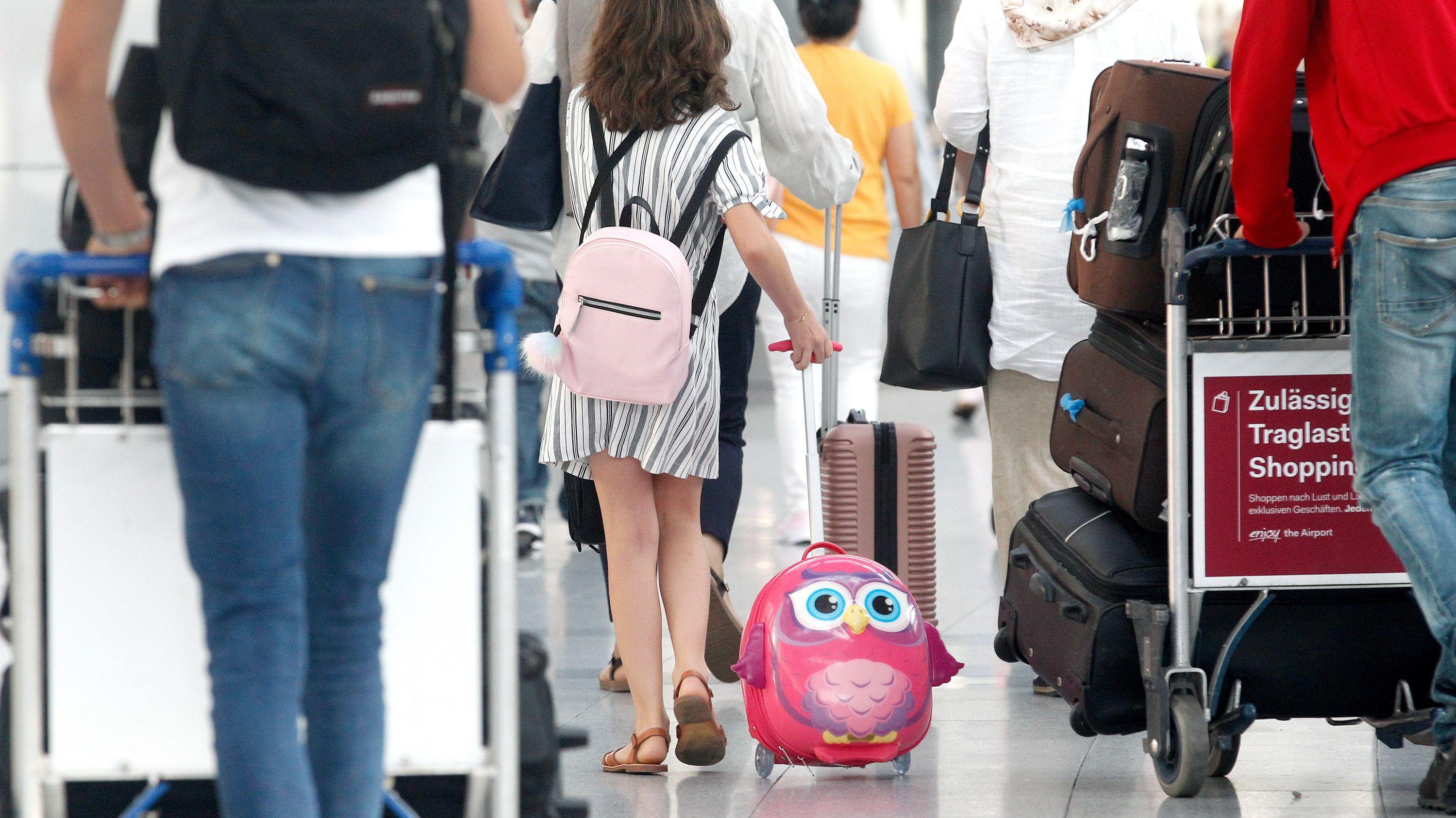 Urlauber am Check-In-Schalter eines Flughafens (Symbolbild)