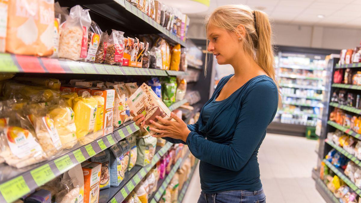 Eine Frau steht in einem Supermarkt vor einem Regal und begutachtet ein Produkt hinsichtlich seiner Inhaltsstoffe.
