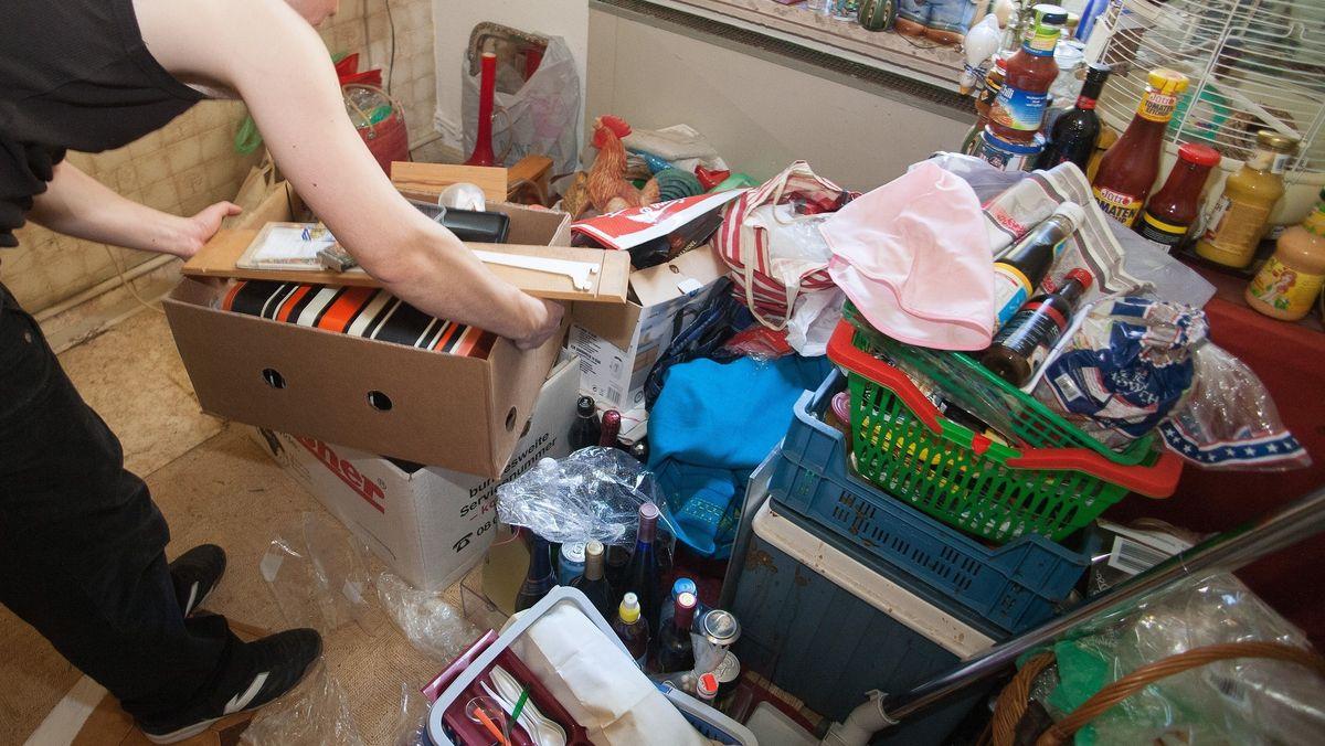 Ein Mitarbeiter eines Umzugsunternehmens entrümpelt ein Zimmer einer Wohnung