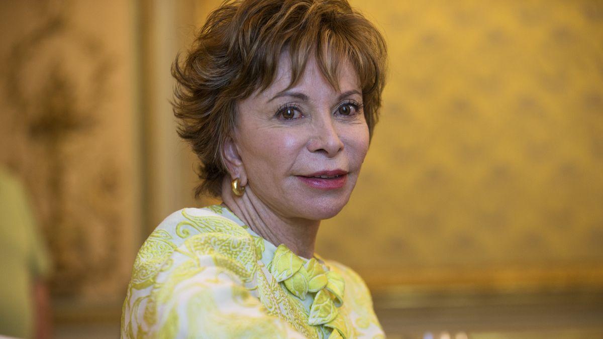 Die Schriftstellerin Isabel Allende schaut in Richtung Kamera, sie trägt einen Goldohrring, Makeup und ein reich besticktes und verziertes Oberteil. Im Hintergrund lässt sich unscharf ein Salon erahnen.