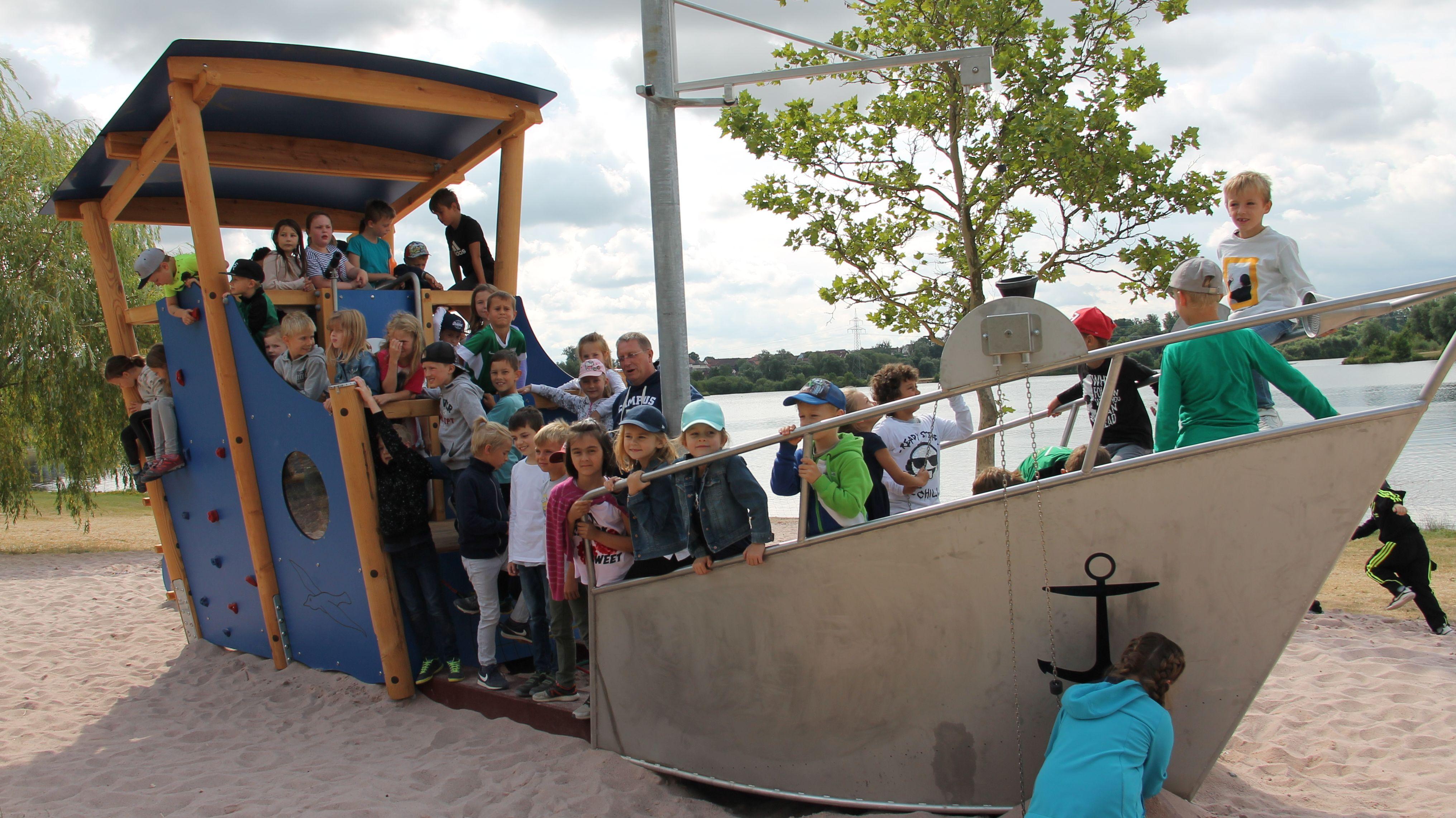 Kinder stehen gemeinsam mit Oberbürgermeister Henry Schramm (CSU) in einem schiffartigen Spielgerät auf dem neu eröffneten Spielplatz in der Kulmbacher Mainaue