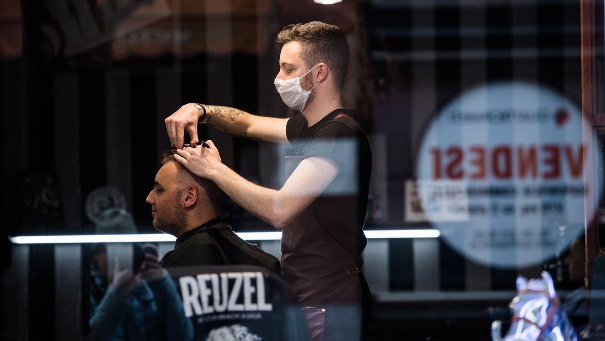 Ein Friseur mit Atemschutzmaske bei der Arbeit am Samstag