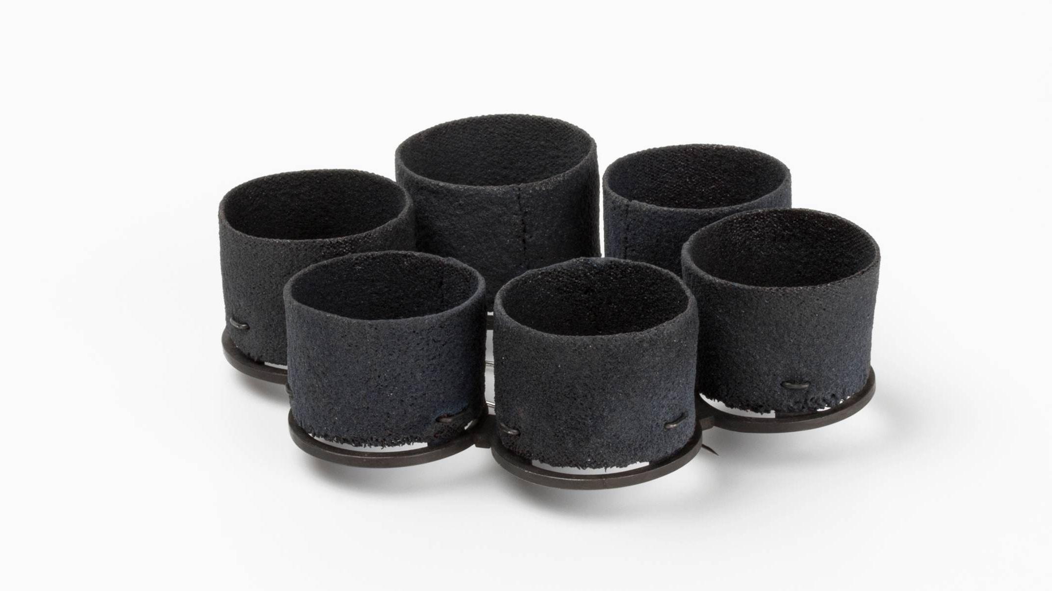Brosche von Christine Graf: sechs kleine, dunkel emaillierte Zylinder in einem Kreis
