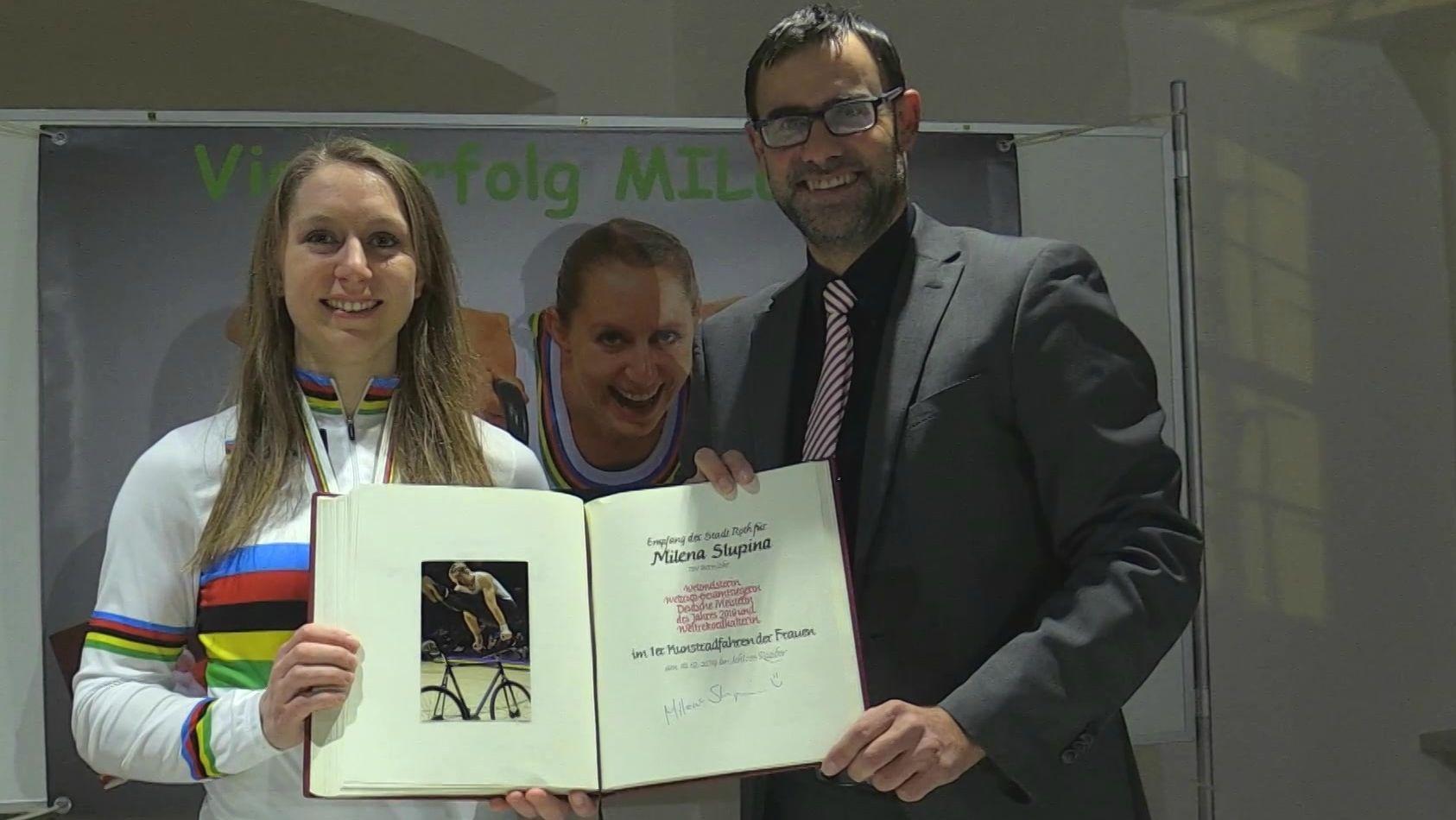 Milena Slupina und Bürgermeister Ralph Edelhäußer halten das Buch