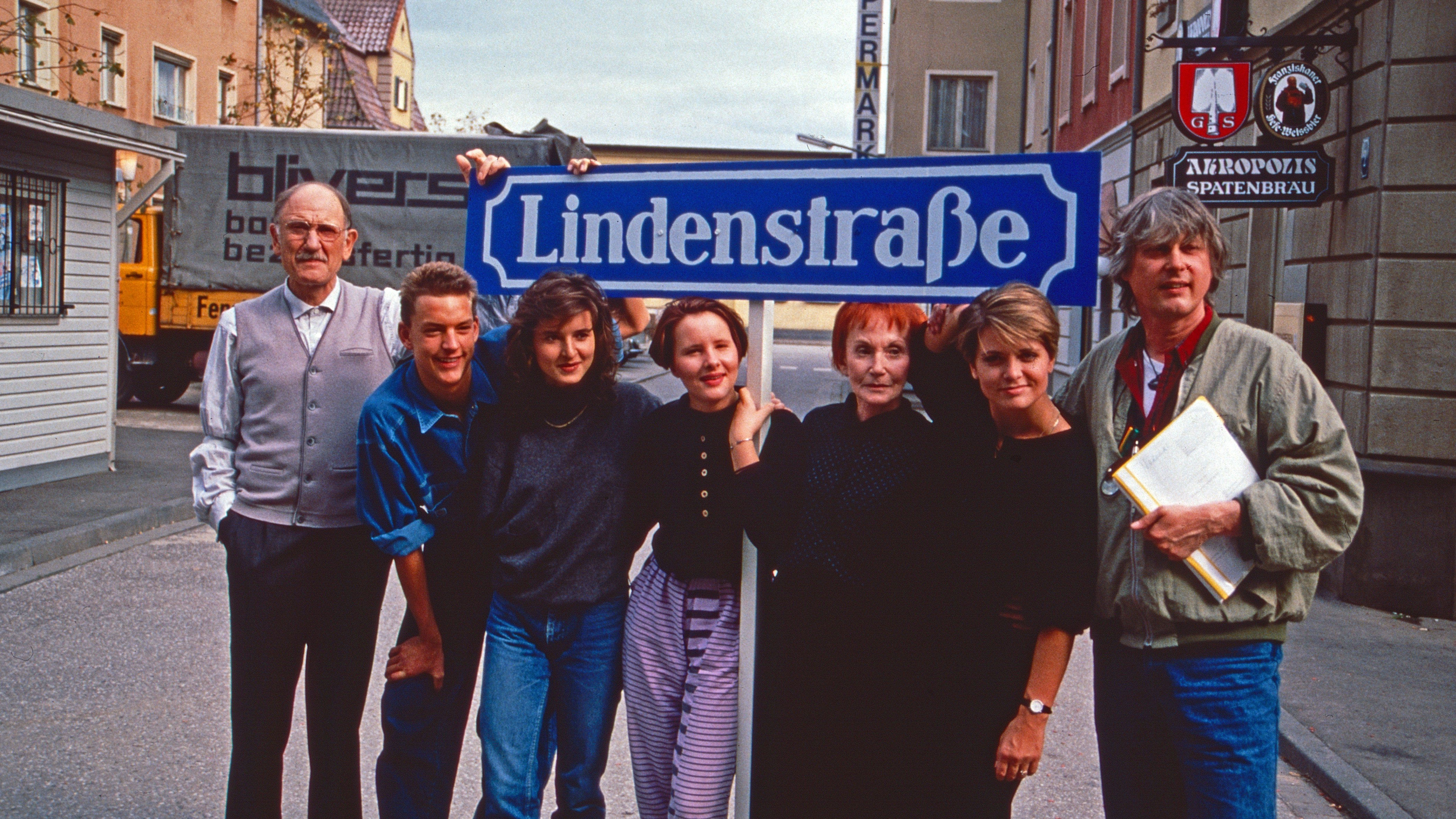 """Die Darsteller der """"Lindenstraße"""" posieren unter dem fikitven Straßenschild (1988)."""
