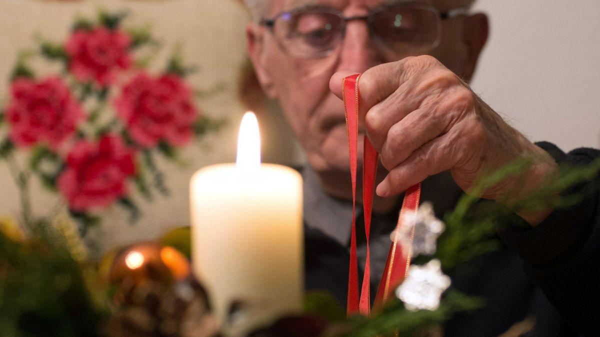 Ein Mann sitzt alleine vor einer Kerze (Symbolbild)
