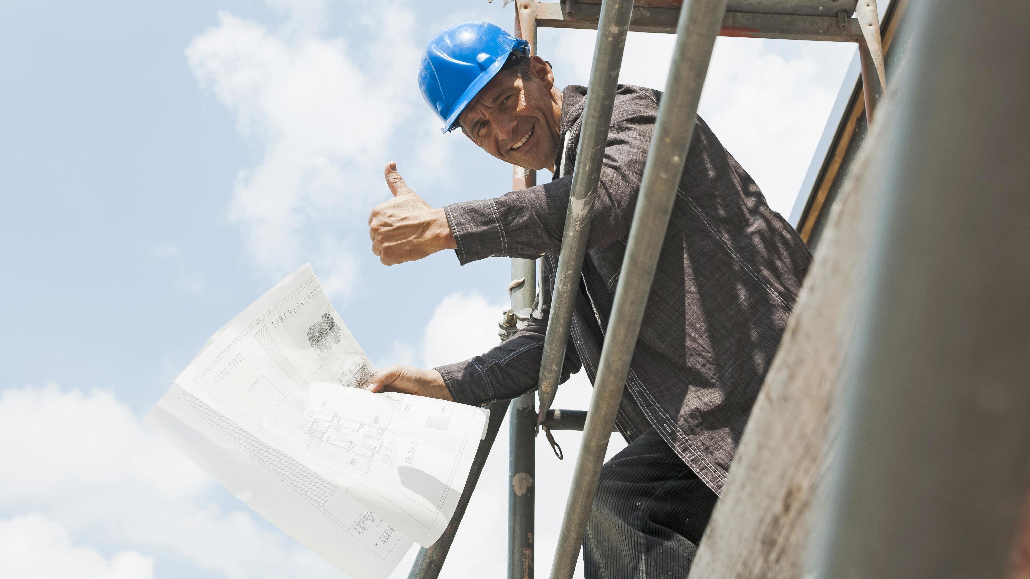 Auf einem Baugerüst steht ein Mann mit Kunsstoffhelm, der den Daumen hebt und lächelt