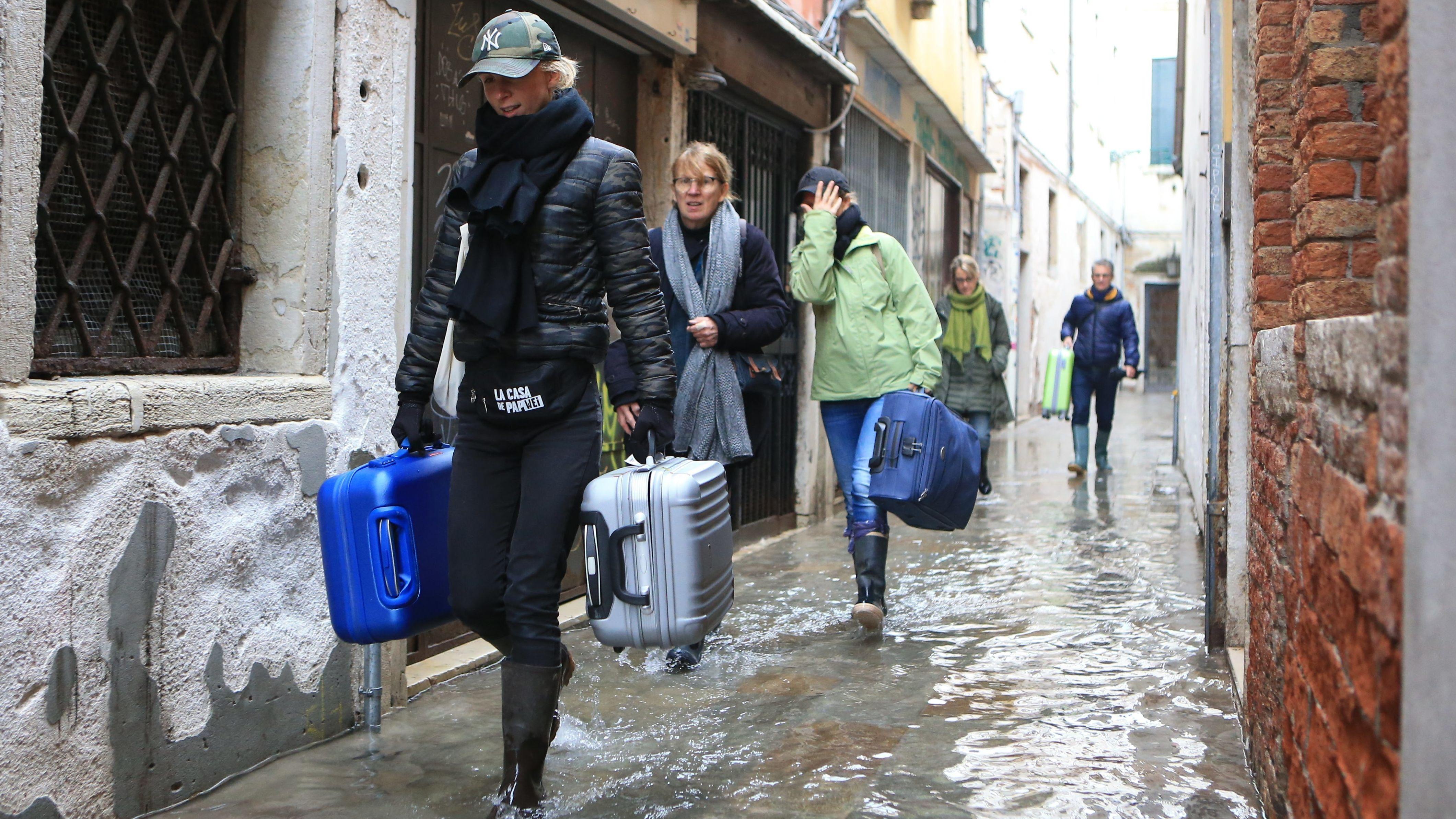 Touristen in Gummistiefen tragen ihre Koffer durch die überfluteten Gassen von Venedig