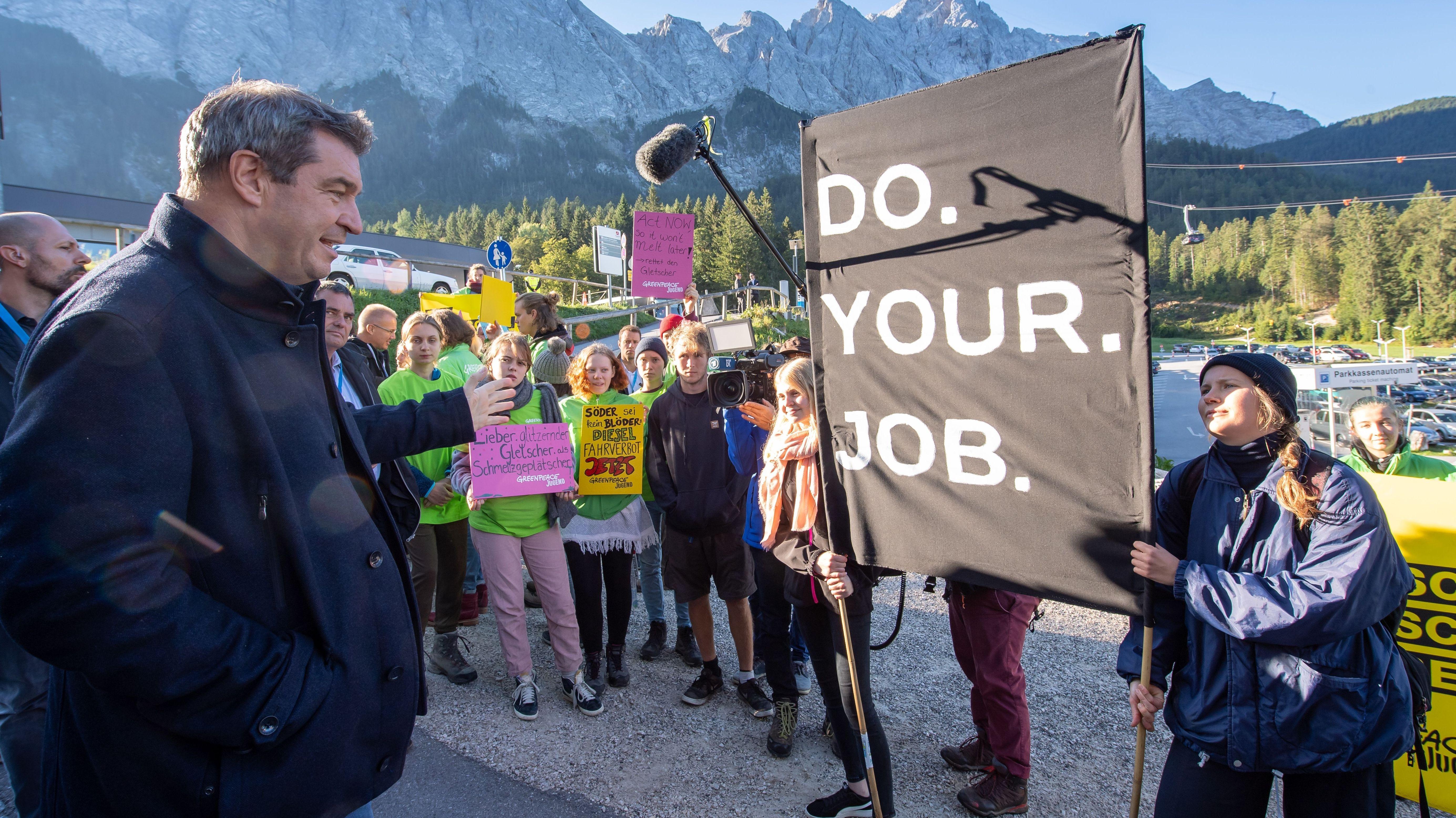 Markus Söder (l., CSU), unterhält sich vor Beginn seiner Klimatour in der Zugspitzregion mit Aktivisten von Greenpeace und Bund Naturschutz