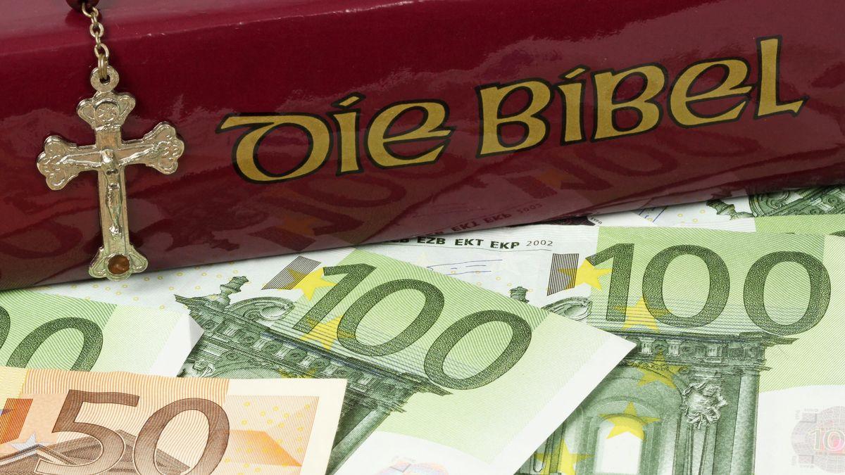 Ein Kruzifix, eine Bibel und Geldscheine