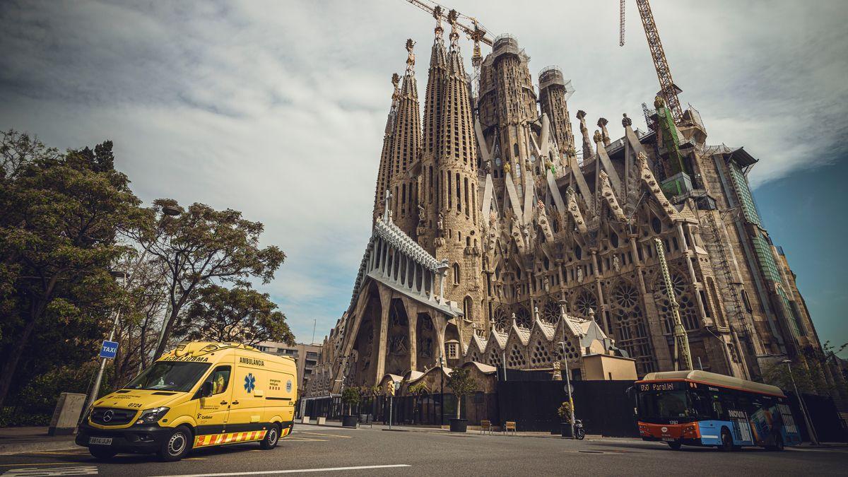 """Barcelona: Ein Krankenwagen fährt an einer fast menschenleeren Straße an der """"Sagrada Familia"""" von Gaudi vorbei."""