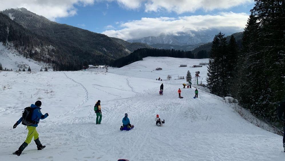 Bayern, Spitzingsee: Rodler und Wanderer sind am 26.12.2020 im Skigebiet Spitzingsee unterwegs. (Archibild)