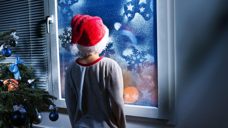 Junge steht vor Fenster und blickt hinaus.