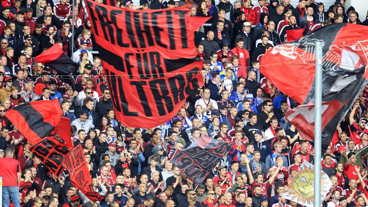 """Nürnberger Ultra-Fans beim Auswärtsspiel in Paderborn. Sie halten eine rote Fahne mit der Aufschrift """"Freiheit für Ultras"""" hoch."""