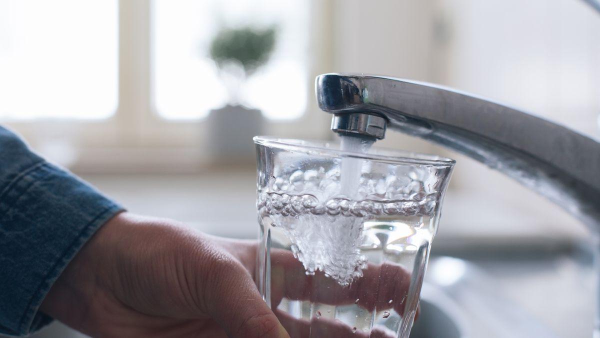 Eine Person füllt ein Glas Wasser unter dem Wasserhahn.