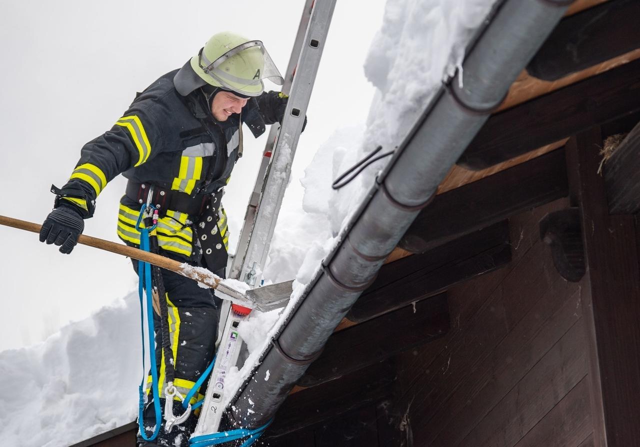 12.01.2019, Bayern, Berchtesgaden: Ein Feuerwehrmann räumt ein mit Schnee überladenes Dach.