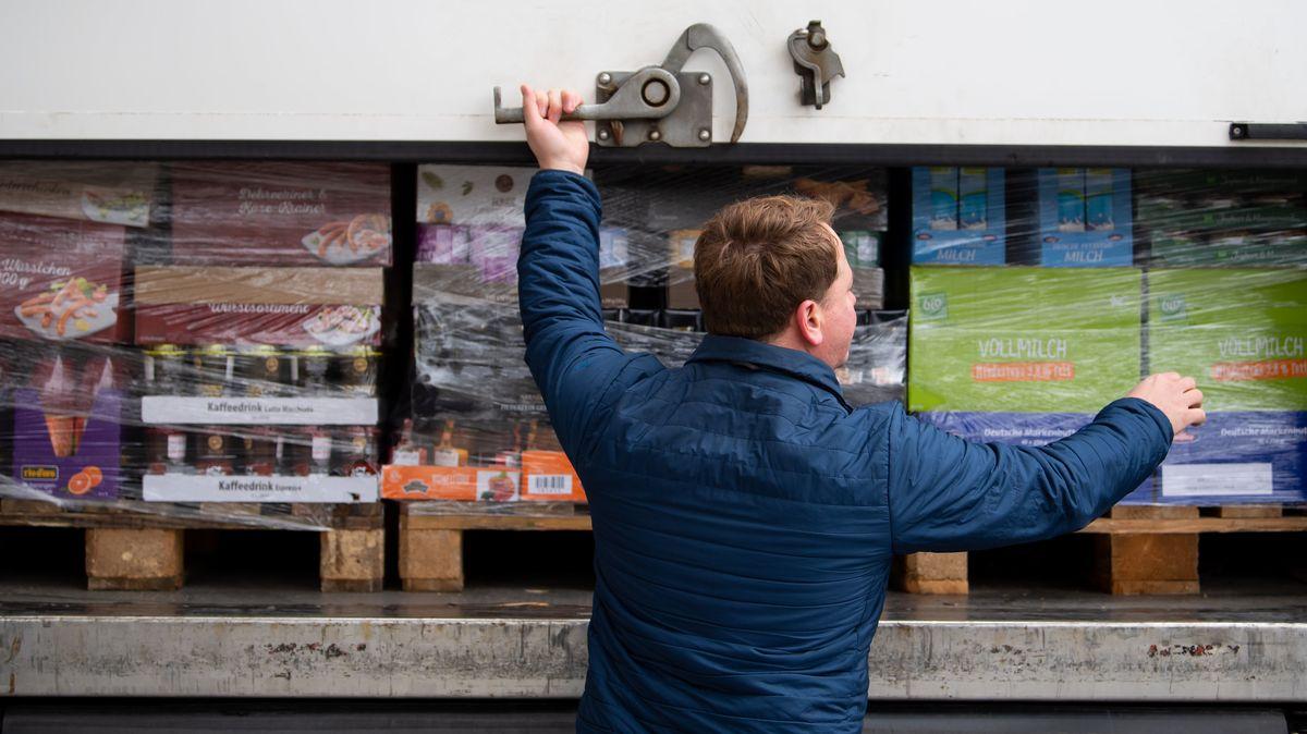 Ein Mitarbeiter eines Logistik-Unternehmens schließt die Ladefläche von einem LKW, der Lebensmittel geladen hat.