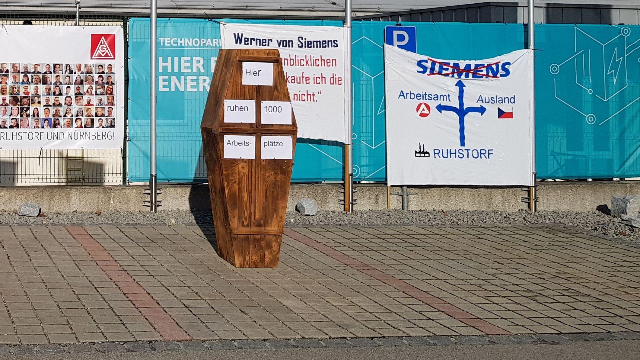"""Ein Holzsarg mit der Aufschrift """"Hier ruhen 1.000 Arbeitsplätze"""""""
