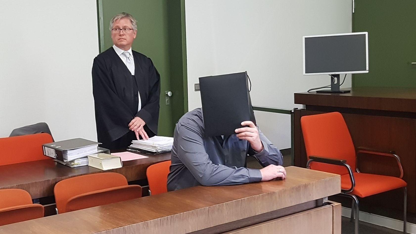 Der Angeklagte verbirgt sich hinter einer Mappe im Landgericht München.