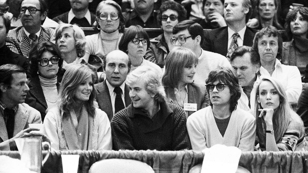 Schwarz-weiß-Aufnahme beim Tennis: Peter Beard sitzt im Publikum in der ersten Reihe,  zusammen mit Mick Jagger und Peter Hall