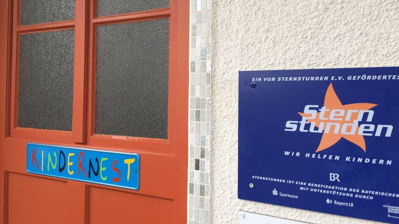 """In bunten Buchstaben steht """"Kindernest"""" auf einem Schild, das an der Haustür des Hauses Immanuel in Thurnau hängt, daneben ein blaues Schild mit dem Hinweis, dass die BR-Sternstunden das Haus Immanuel unterstützen."""