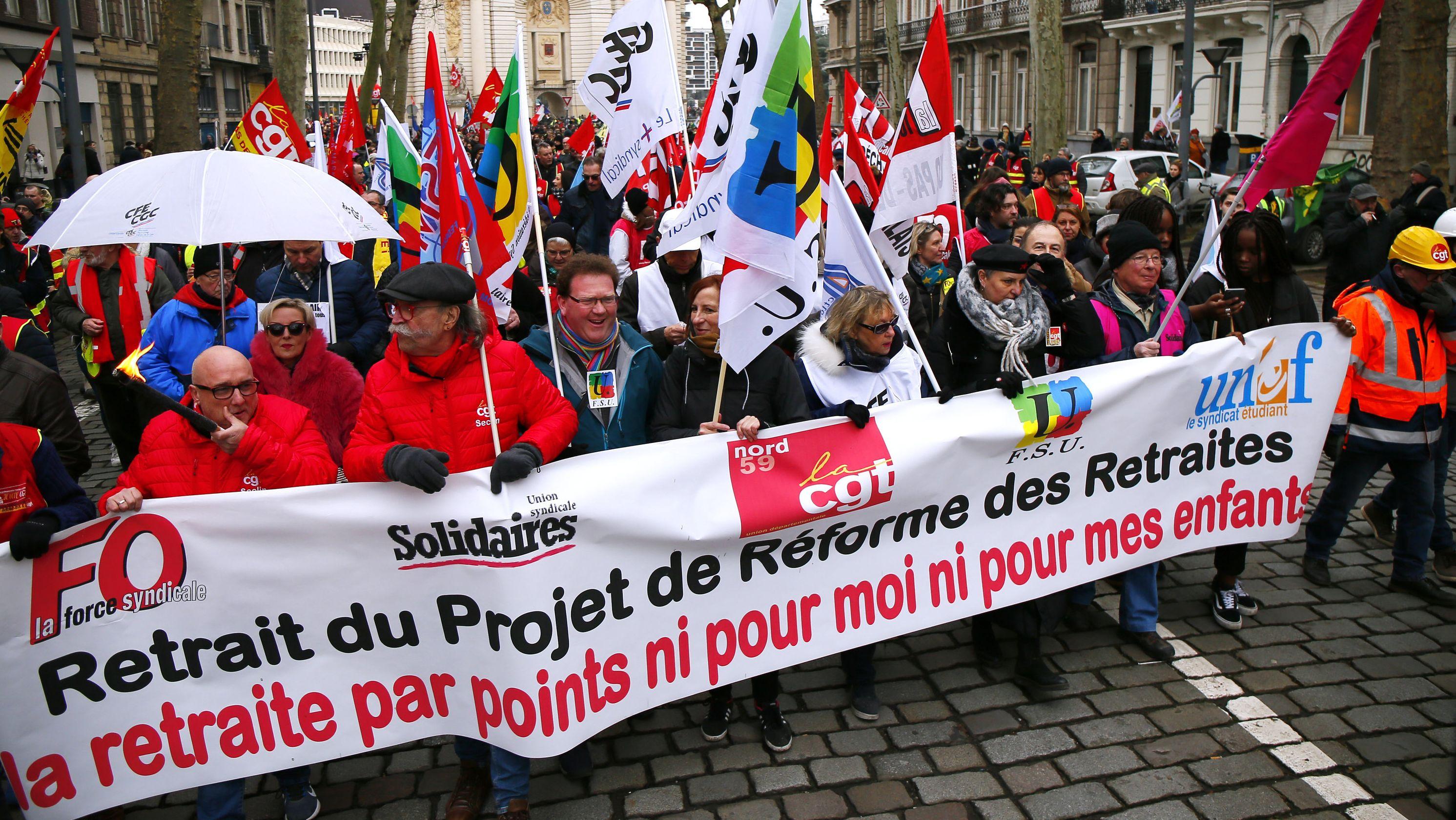 """Demonstranten halten während eines Protestes gegen die geplanten Rentenreformen Fahnen und einen Banner mit der Aufschrift """"Retrait du Projet de Reformes des Retraites"""" (""""Stoppt das Projekt der neuen Rentenreform"""")."""
