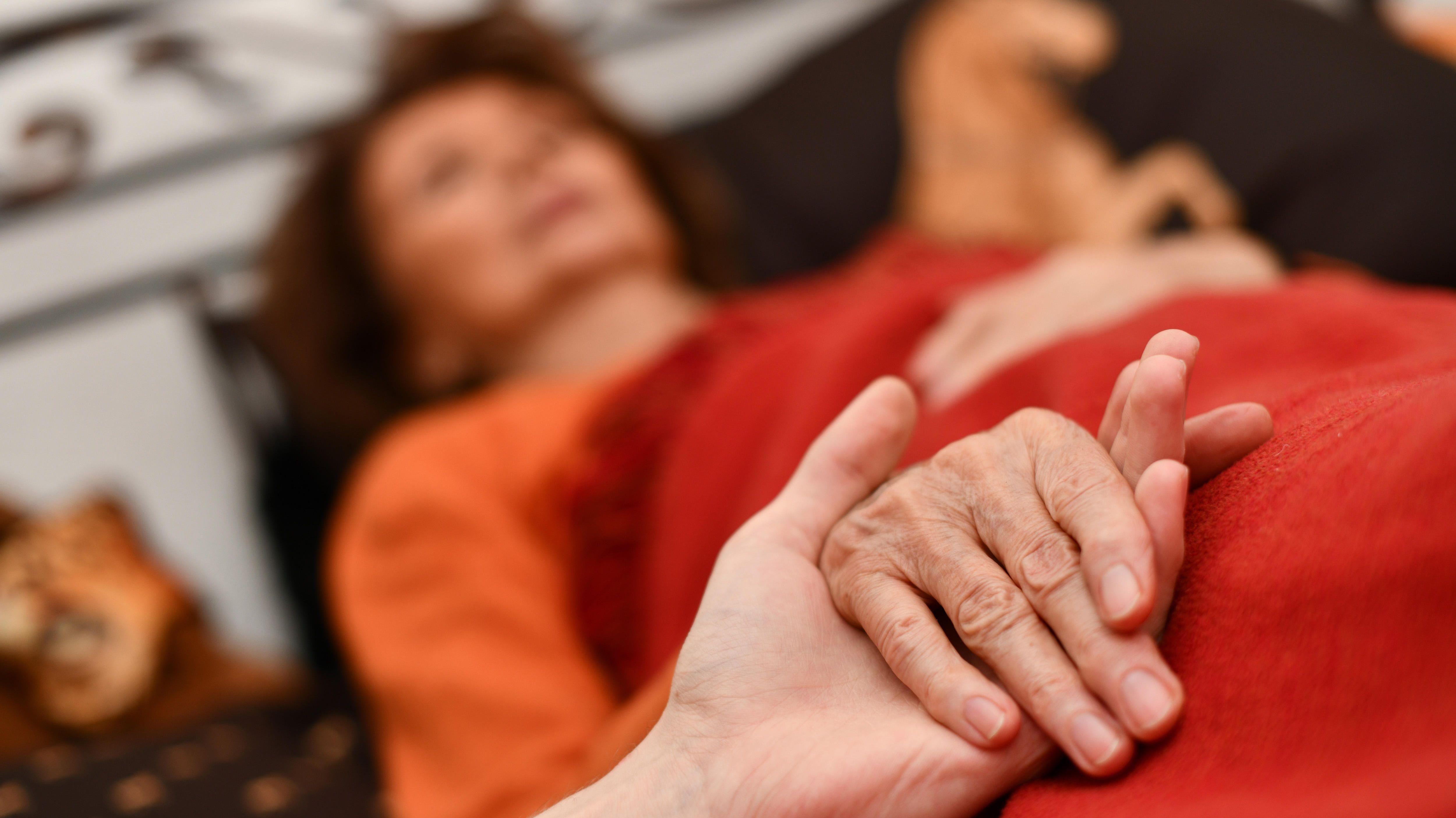 Symbolbild für Sterbehilfe: Zwei Hände, die sich umfassen