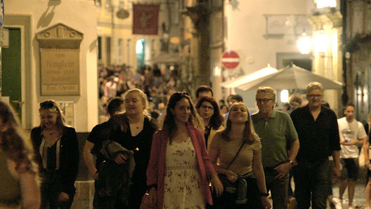 Blick in die Bamberger Sandstraße bei Nacht. Viele Menschen sind dort unterwegs.