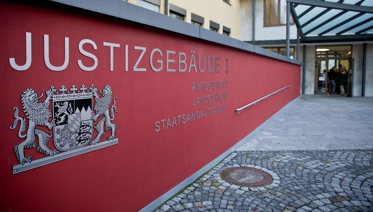 """Auf einer roten Mauer vor dem Landgericht Coburg ist unter anderem """"Amtsgericht, Landgericht und Staatsanwaltschaft"""""""