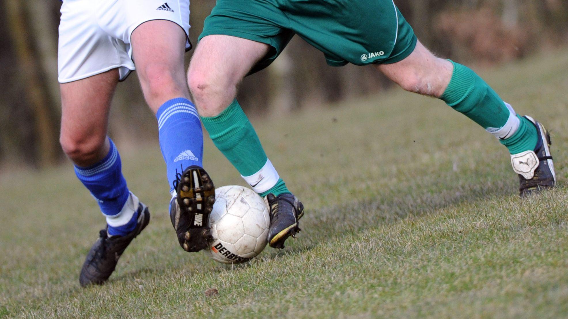 Beine von Amateurfußballern und Fußball