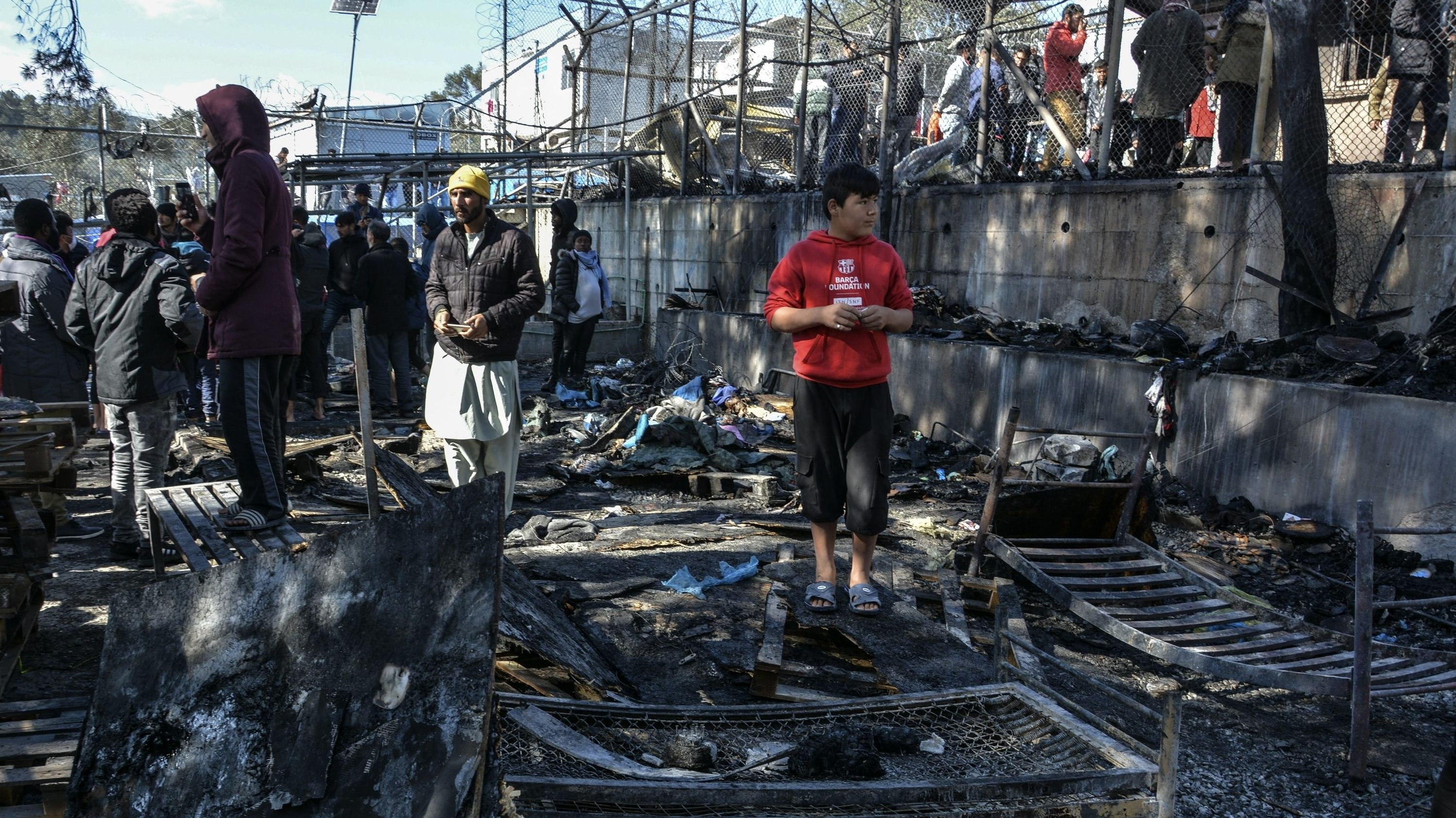 Migranten stehen auf den abgebrannten Überresten eines Containerhauses