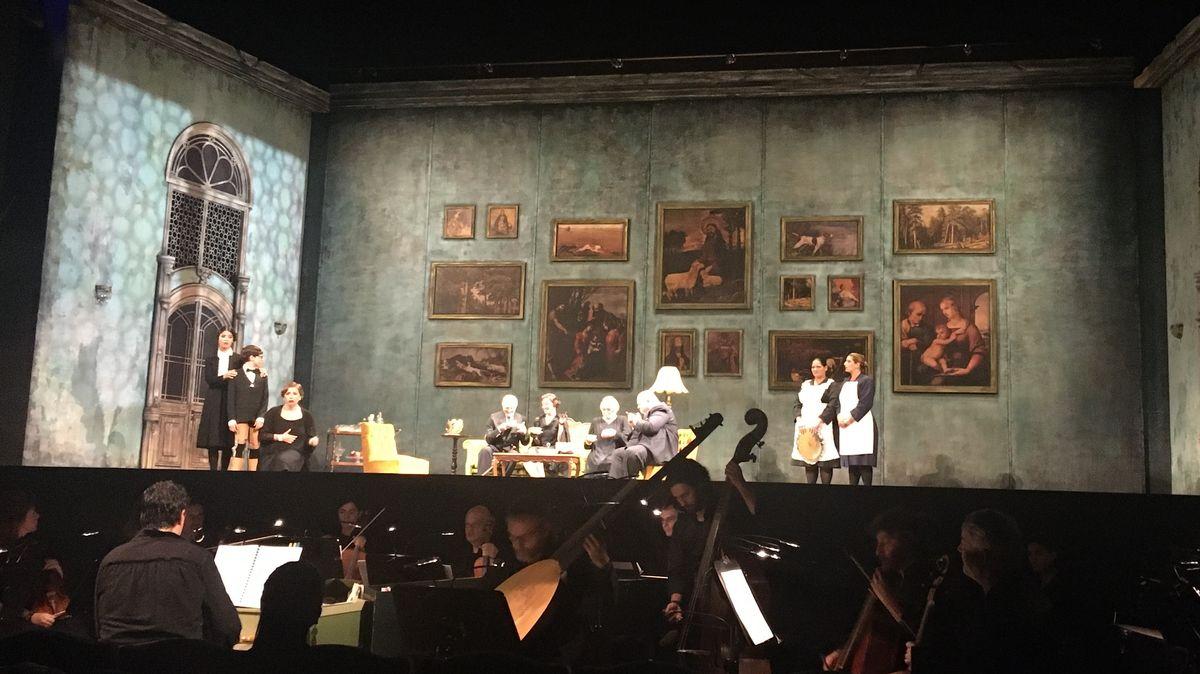 Auf der Bühne sitzen die Schauspieler an einem Tisch, daneben stehen Kammerzofen, davor sind die Musiker im Orchestergraben zu sehen.