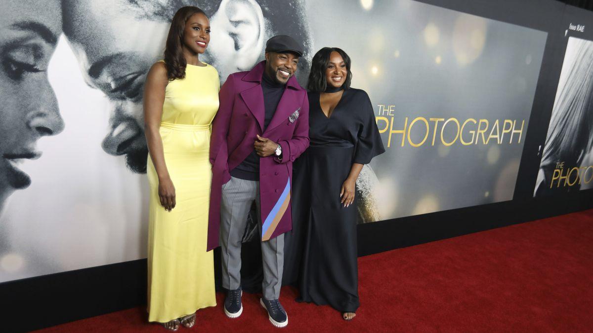 """Drei Menschen stehen vor dem Filmplakat von """"The Photograph"""", es handelt sich um Issa Rae, Will Packer und Stella Meghie bei der Weltpremiere von  """"The Photograph"""" in New York"""