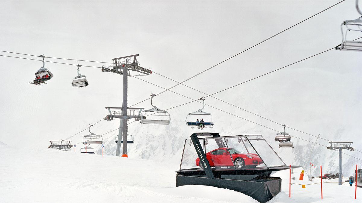 Ein Skilift in den verschneiten Bergen, darunter ein roter Porsche in einem gläsernen Schaukasten