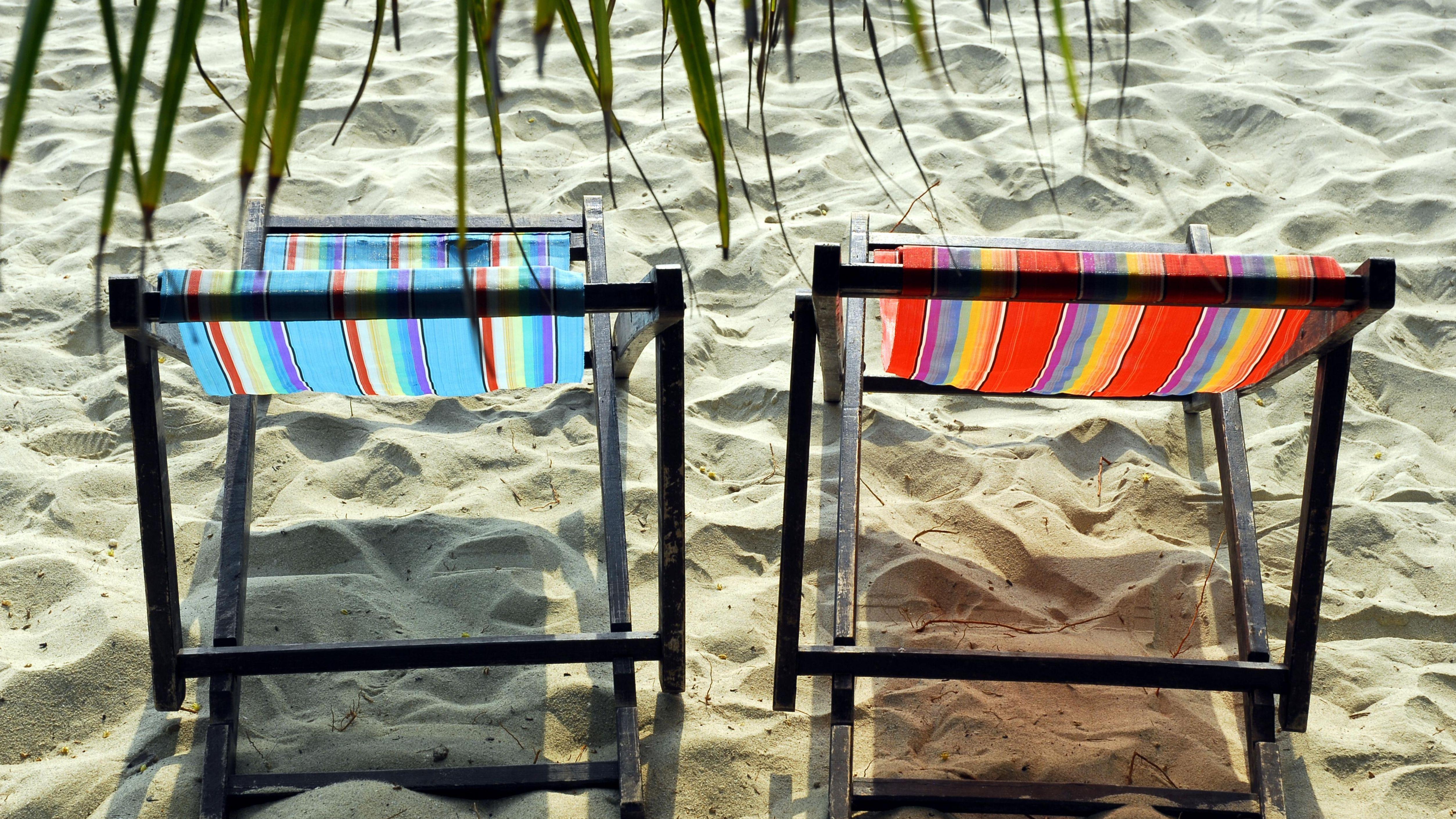 Zwei leere Liegestühle am Sandstrand unter Palmen. Symbolfoto.