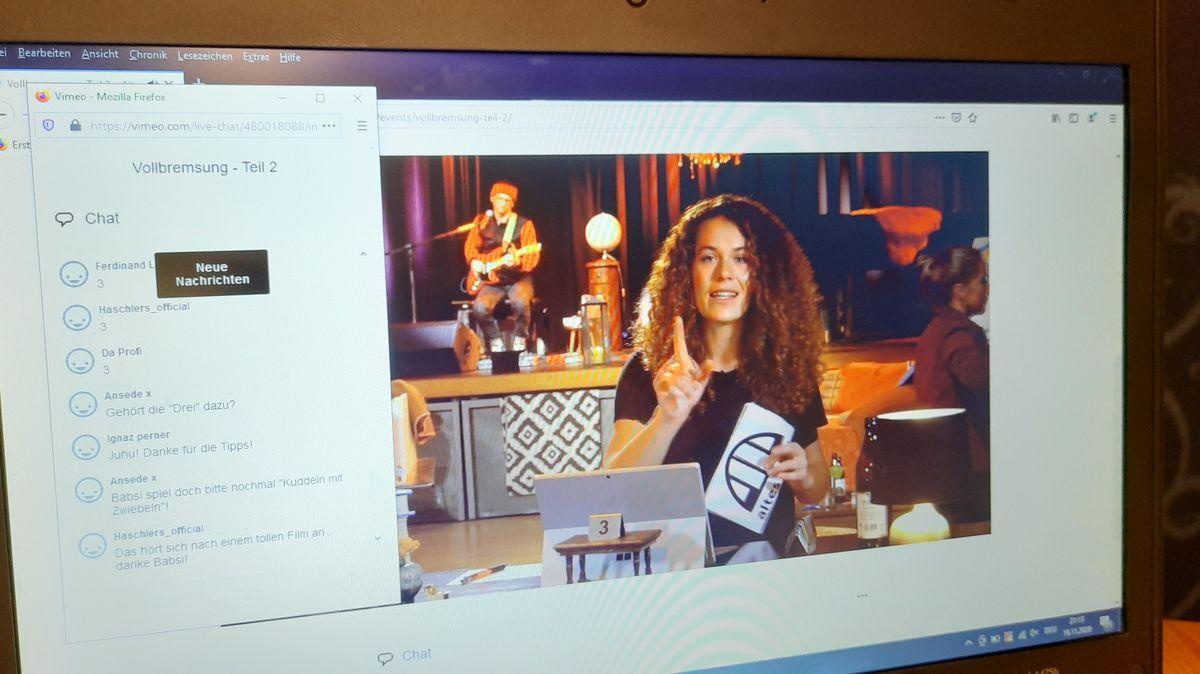 Ein Laptop-Bildschirm, darauf zu sehen die Szene eines Livestreams. Im Hauptbild die Moderatorin Violetta Ditterich, am linken Rand der geöffnete Chat, der zum Livestream gehört.