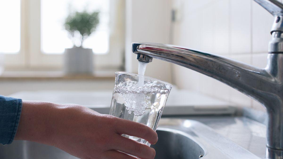 Jemand füllt am Wasserhahn ein Glas mit Leitungswasser