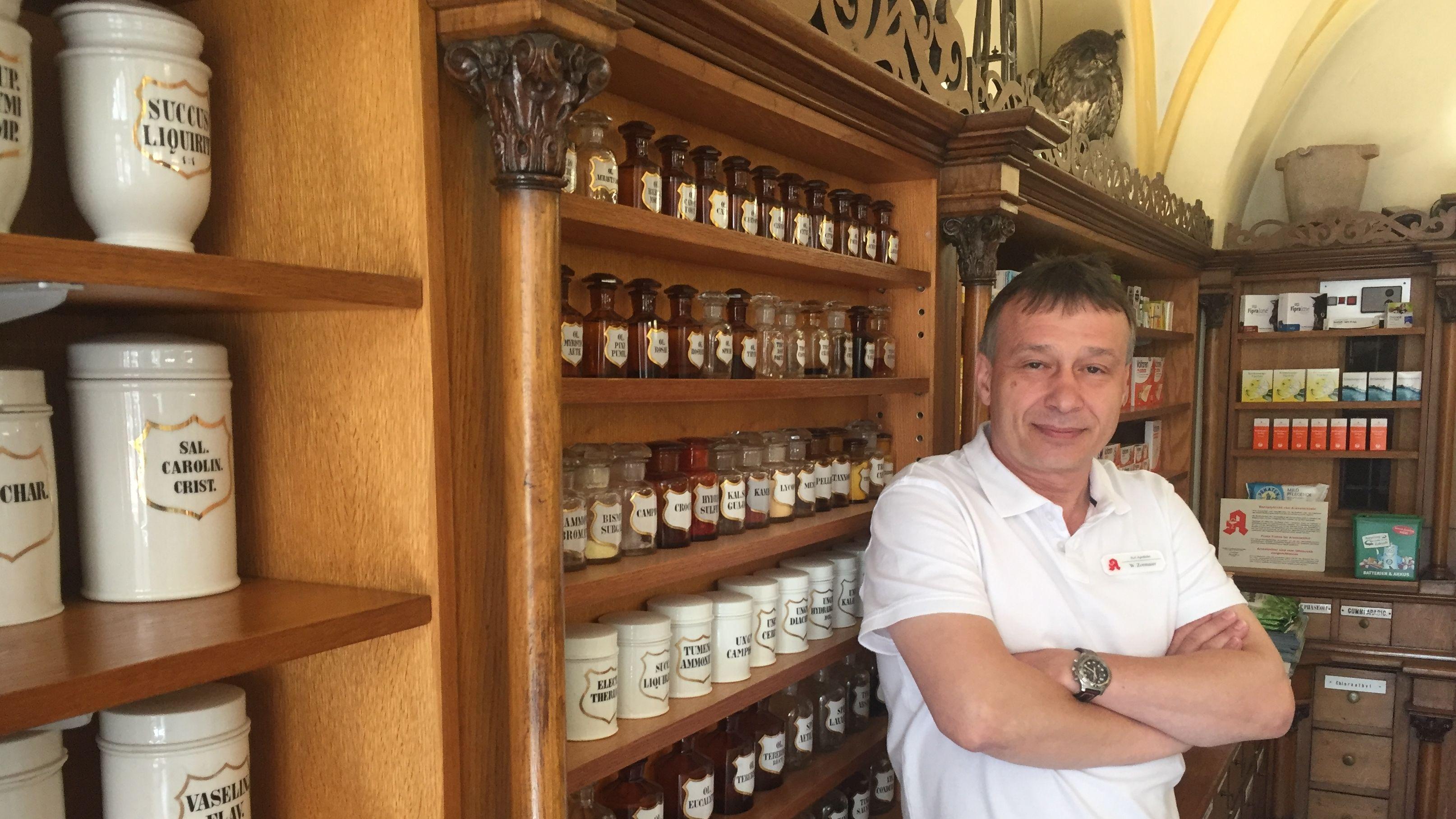 Wolfgang Zormaier, Chef der Passauer Apotheke, vor einem kunstvoll geschnitzten Regal