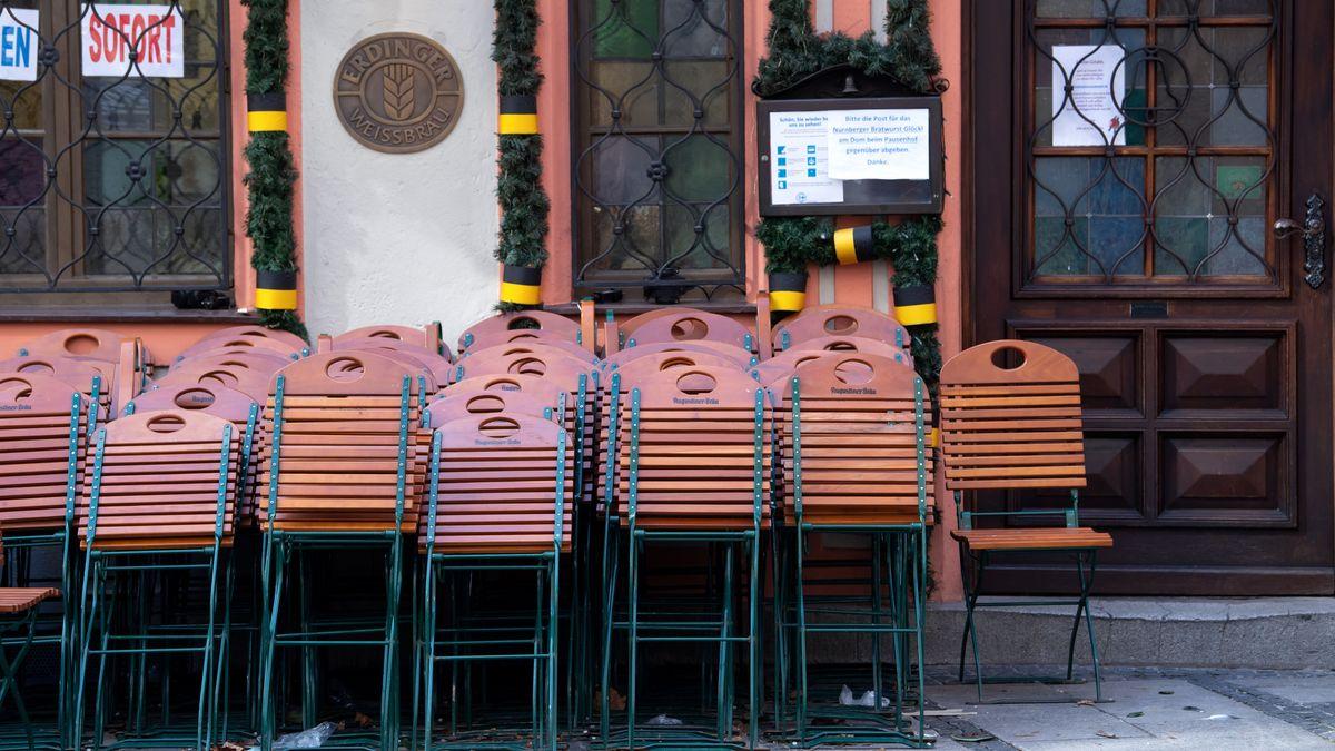 Tische und Stühle stehen vor einem geschlossenen Restaurant in der Innenstadt Münchens.