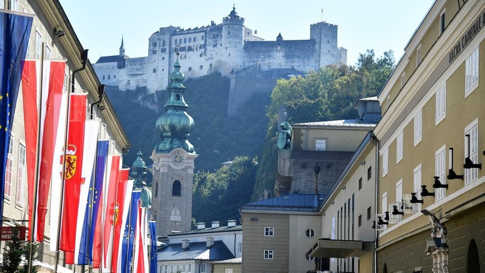 Österreichische und EU-Fahnen hängen vor einem Gebäude in Salzburg. Darüber ist die Festung Hohensalzburg zu sehen. | Bild:dpa-Bildfunk/Barbara Gindl