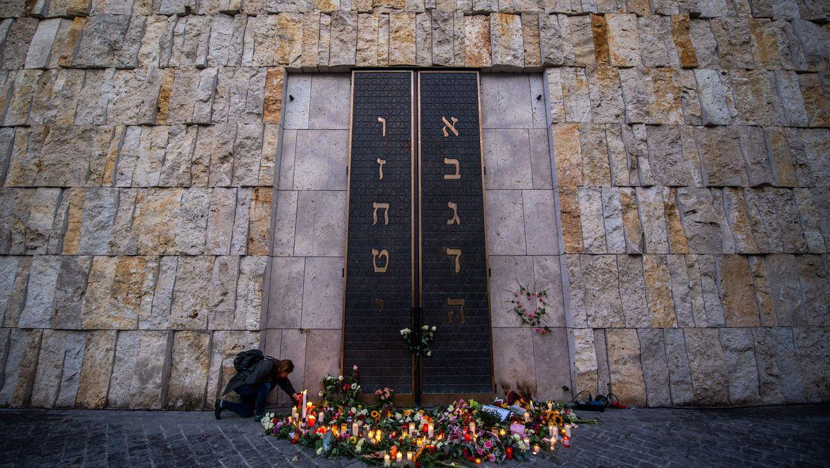 Eine Frau zündet vor der Münchener Synagoge eine Kerze an, um Solidarität nach den Angriffen in Halle/Saale zu zeigen