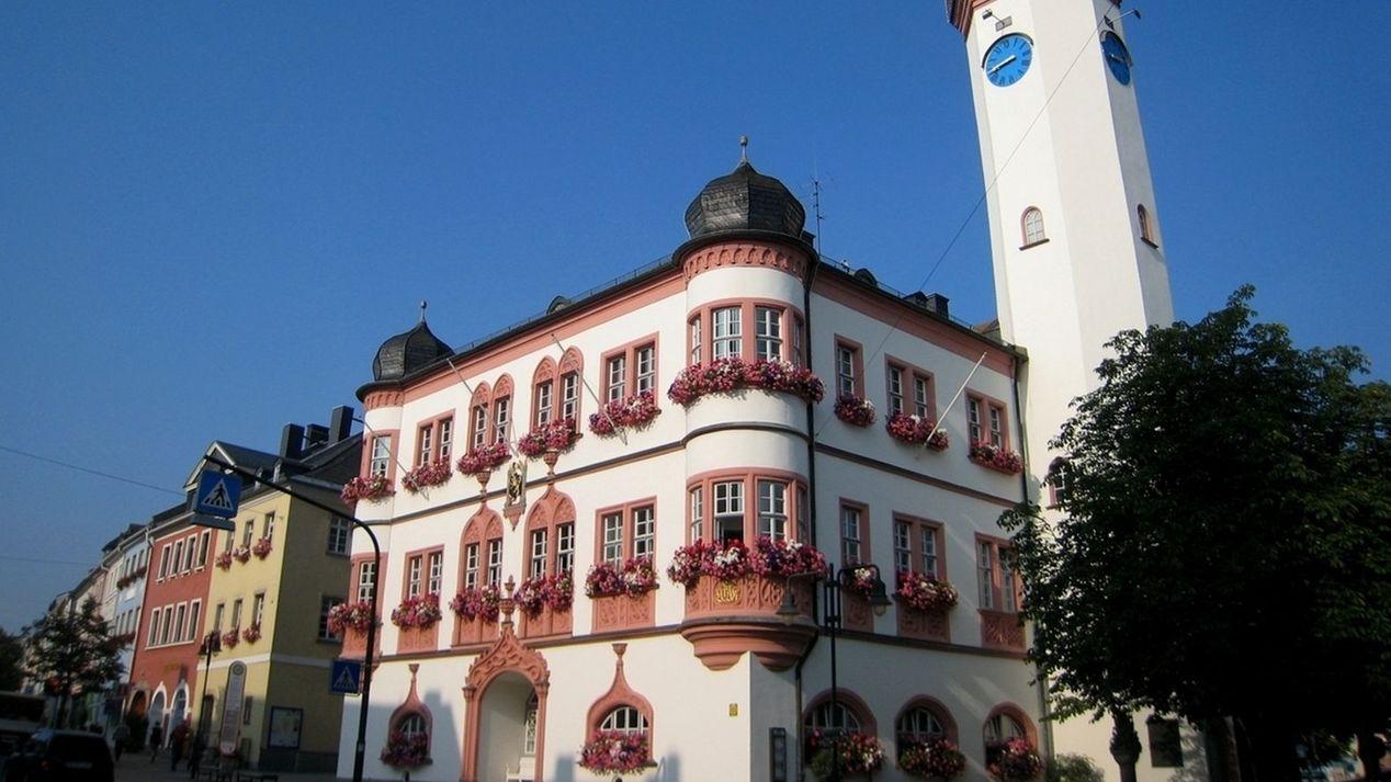 Die Fassade de Hofer Rathauses mit den zwei Zwiebeltürmchen und dem Turm mit einer blauen Uhr.